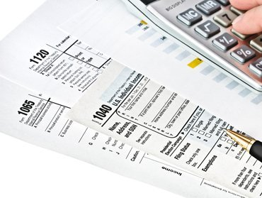 tax forms spread out with a pen and calculator